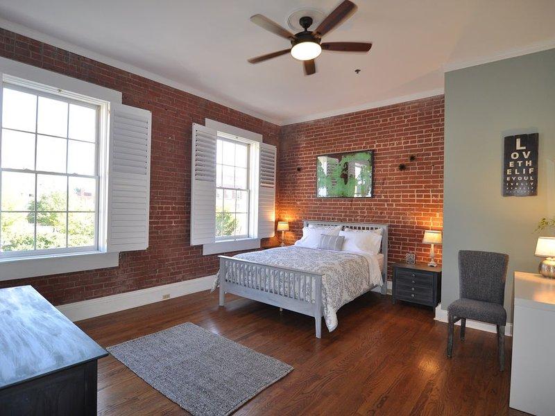 Una reina cómodo tamaño cama en un dormitorio amplio, soleado