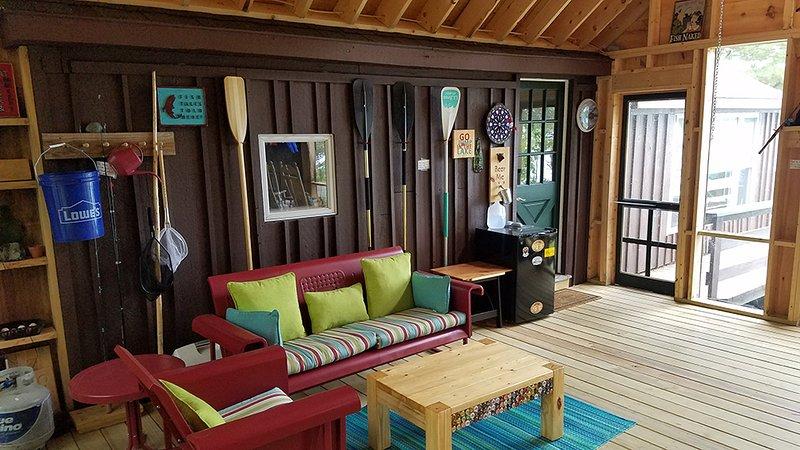 Verbazingwekkende afgeschermde veranda woonkamer die beide hutten verbindt