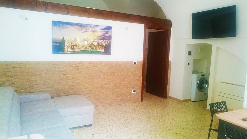 Sitting room with premium sofa and large Smart-TV, air conditioner + washing machine + full kitchen