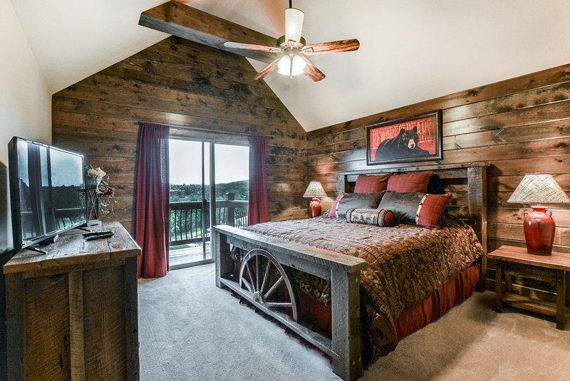El dormitorio principal de arriba con TV LCD plana y muebles rústicos.