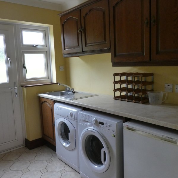 Utility room with washing machine,tumble dryer,freezer, access to patio and broom cupboard.