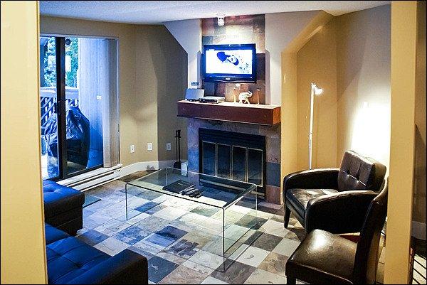 Njut av det soliga vardagsrummet med vedeldad eldstad, stor plattskärms-läder soffa