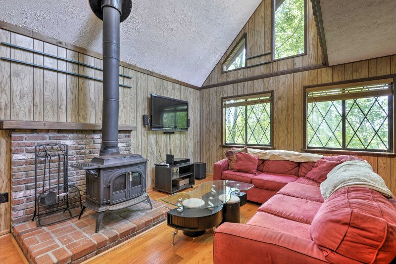 The interior of the home offers vaulted ceilings, a wood-burning stove, and beautiful decorative glass windows.