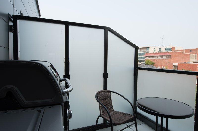 balcón nivel principal con barbacoa y asientos para dos.