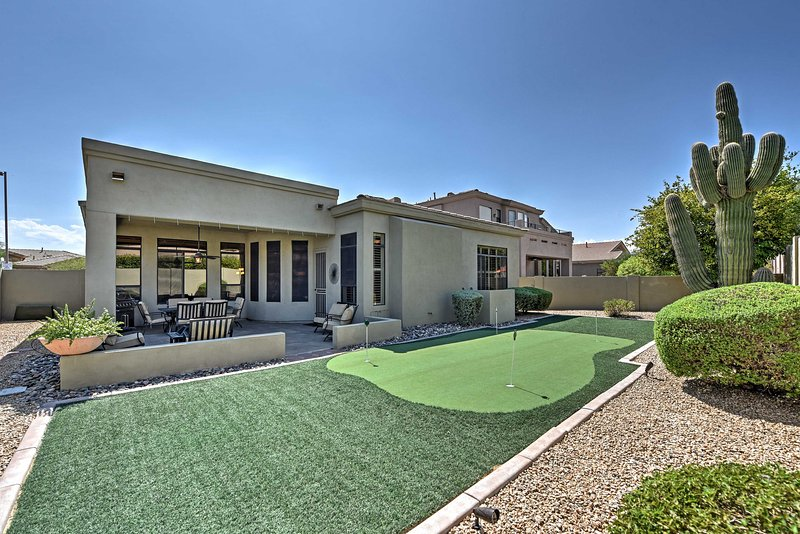 Lounge in a backyard patio during your stay at this vacation rental house.