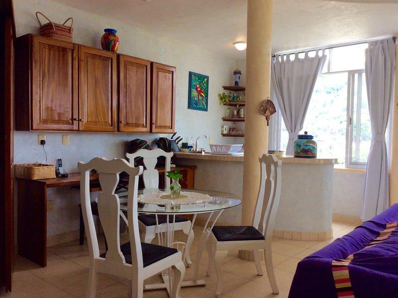 Una cocina con nevera, placa eléctrica, licuadora, tostadora, microondas, cafetera, wok eléctrico, etc.