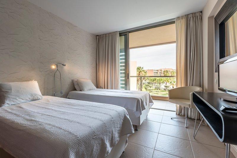 La habitación doble, abriendo en el balcón, con vistas a las piscinas.