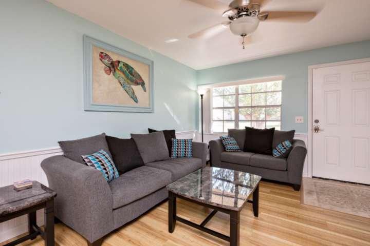 sala de estar cuenta con un sofá, sofá de dos plazas, mesa de centro y mesa auxiliar.
