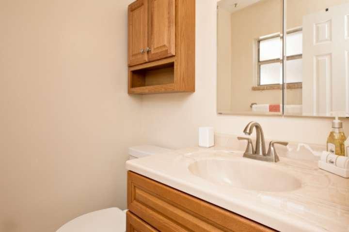 medio baño principal con tocador y baño.