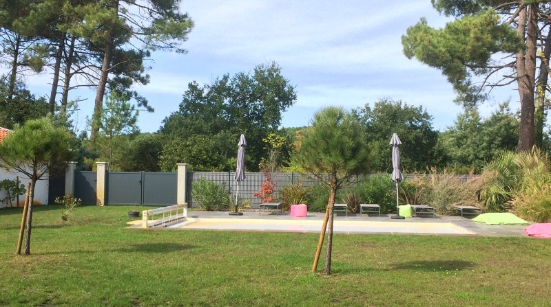 El jardín y la piscina de 4x8m, con cortina protectora, tumbonas, sombrillas ...