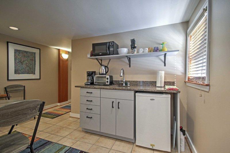 Esta cocina se completa con una pequeña nevera, microondas, cafetera y estufa eléctrica.