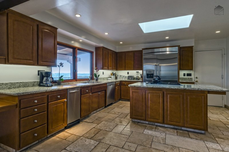 The fully-stocked kitchen has granite countertops, stainless steel appliances with Bosch dishwasher, and great views.