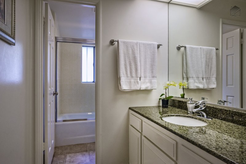 This bathroom with single sink and shower/tub is adjacent to Guest Bedroom #5.