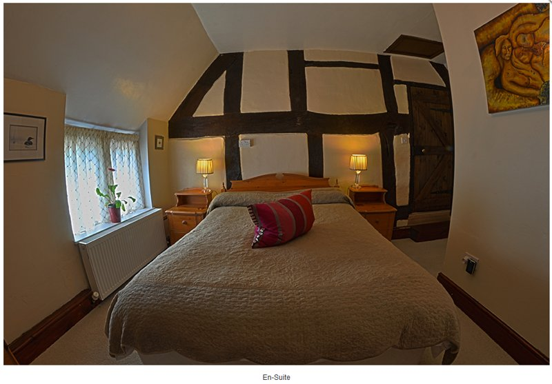 Kingsize bed against 400 year old oak timber frame wall.