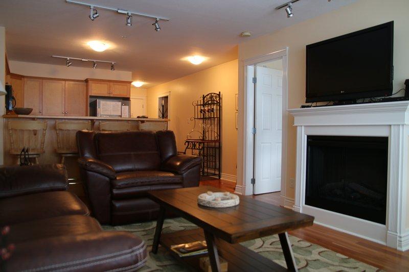 # 209 Salon avec cheminée, TV, regardant à travers la cuisine.