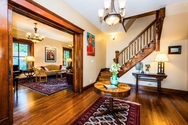 Entry foyer with original beveled-blass pocket doors, trim, floor and main staircase.