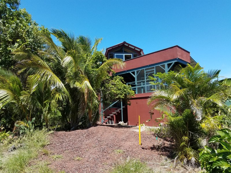 front of house showing upper, open lanai, lower, screened lanai, parking, and entrance stairs.