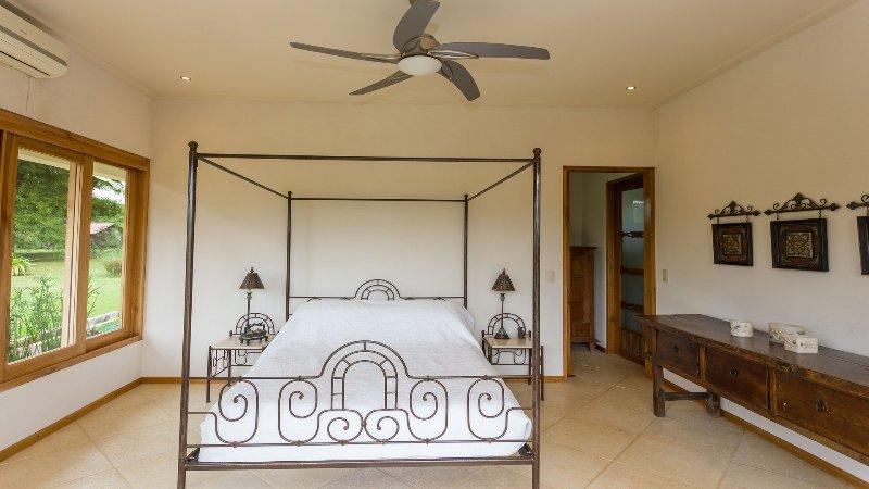 dormitorio de matrimonio con baño en suite, aire acondicionado con ventiladores de techo
