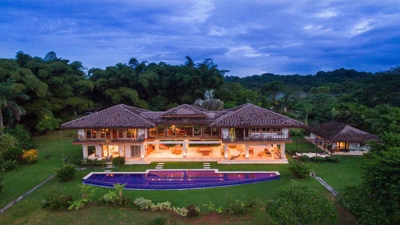 La villa brilla en la noche en el entorno de selva tropical