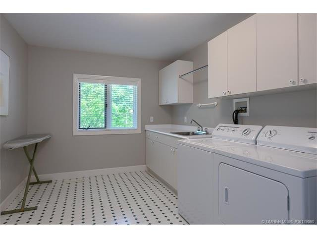 Large fully equipped laundry room with iron, ironing board and drying rack.