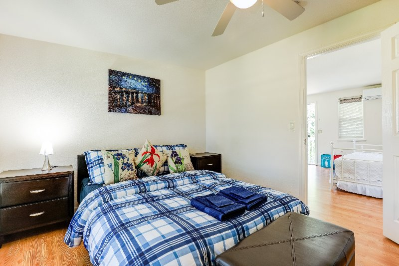 The bedroom is furnished with a comfortable queen bed. The room has a large window.