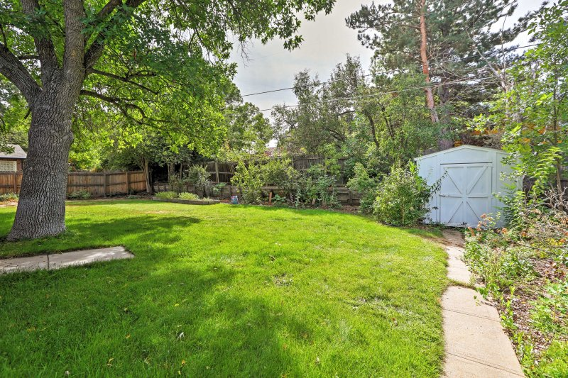 Surrounded by towering trees and a wood fence, the backyard offers plenty of shade and privacy.