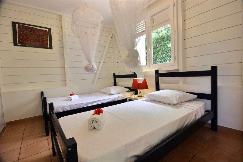 habitación doble con aire acondicionado y mosquiteros en el bungalow