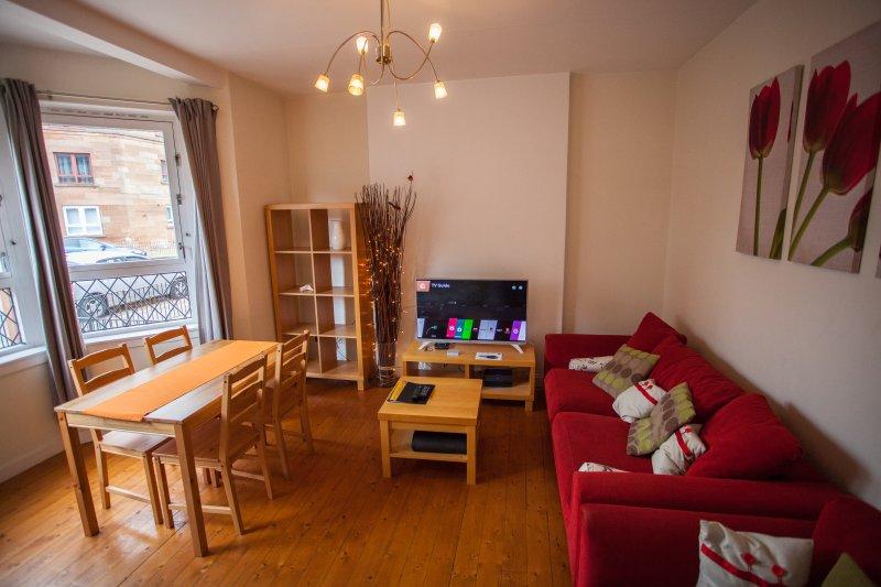 sala de estar con televisión y mesa de comedor conjunto