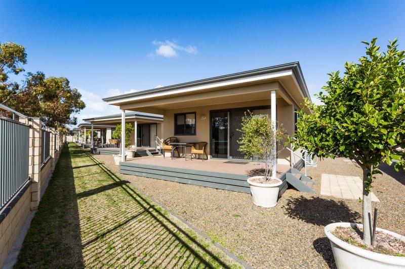 Vorderseite der Villa zeigt Deck und Rasenfläche.