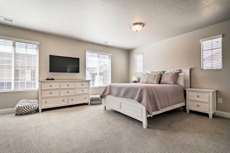 Legen Sie sich auf dem Queen-Bett zurück, wie Sie das Flachbild-TV mit Roku im zweiten Schlafzimmer sehen.