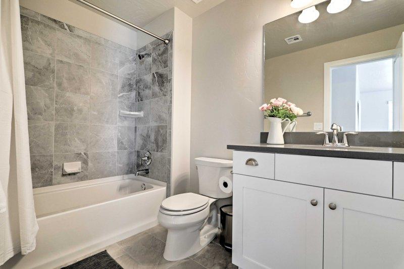 Waschen Sie im zweiten Schlafzimmer mit Bad im Bad auf, ausgestattet mit einem einzigen Waschtisch und Dusche / Badewanne Combo.