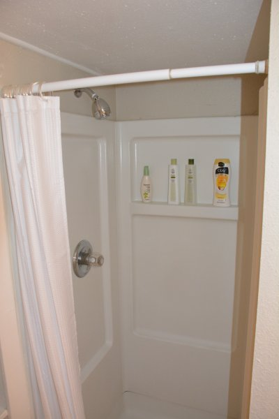 Standing shower in bathroom with face & body wash, and shampoo & conditioner.