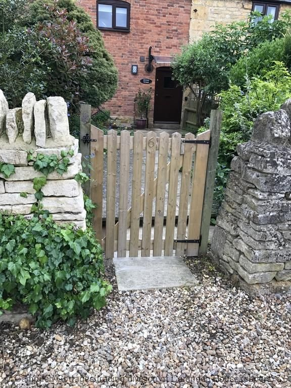 Entrance through original dry stone wall and wooden gate.  Established plants. Bistro table, chairs