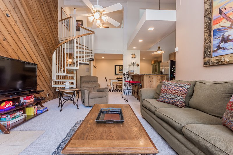 Open concept living room, dining area and stairs to loft