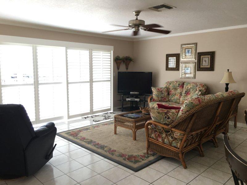 luminoso salón con muebles cómodos junto a la playa y HDTV de pantalla plana grande