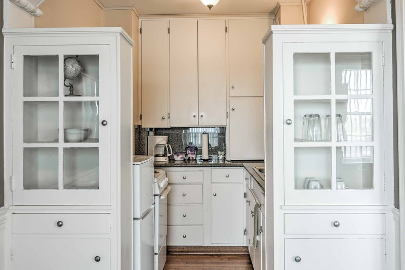 The well-equipped kitchenette features custom cabinets, a stovetop and oven.