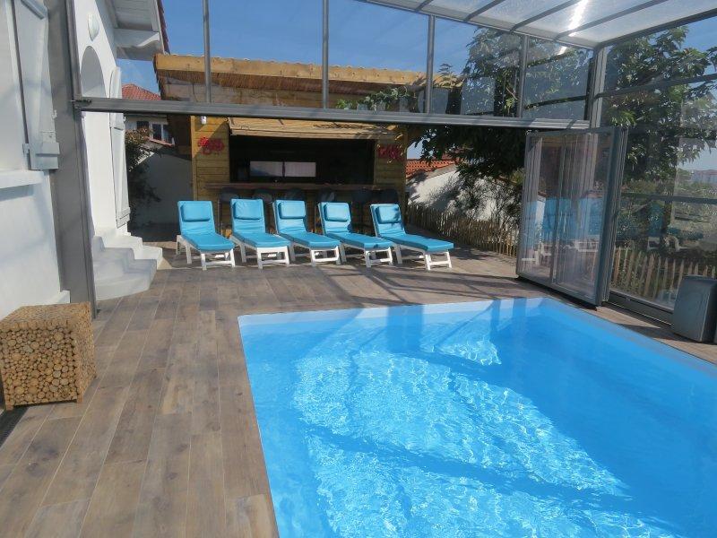 VU piscine chauffée  couverte ou entièrement ouverte en fonction du climat avec  bar bbq en fond