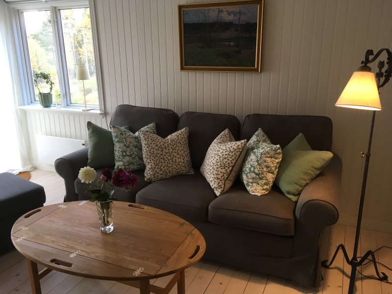 Gran sofá en la sala de estar con capacidad para 4 y se enfrenta a la chimenea.