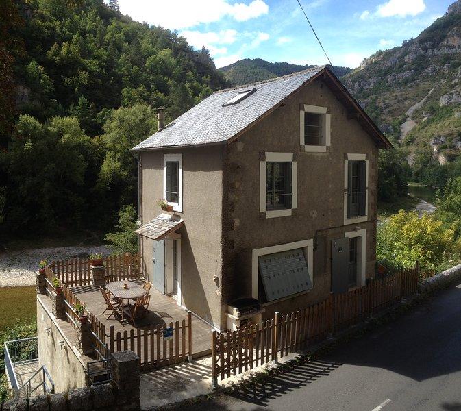 La maison avec la terrasse accessible directement depuis la route et en bord de rivière.