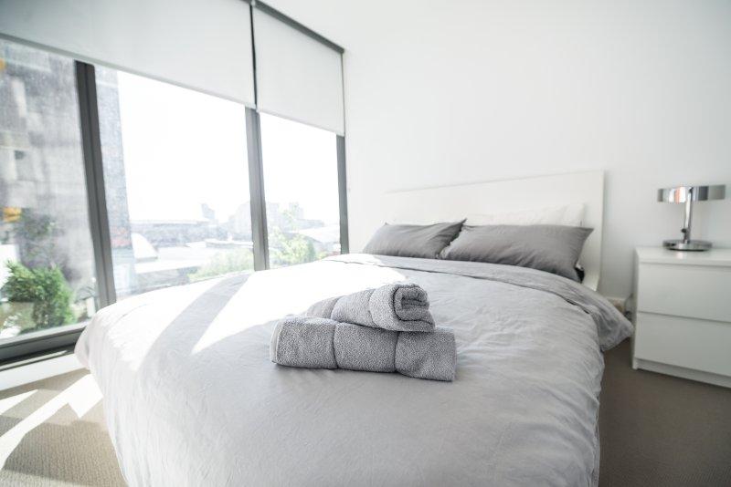 Een slaapkamer met een queen size bed en zachte kussens.