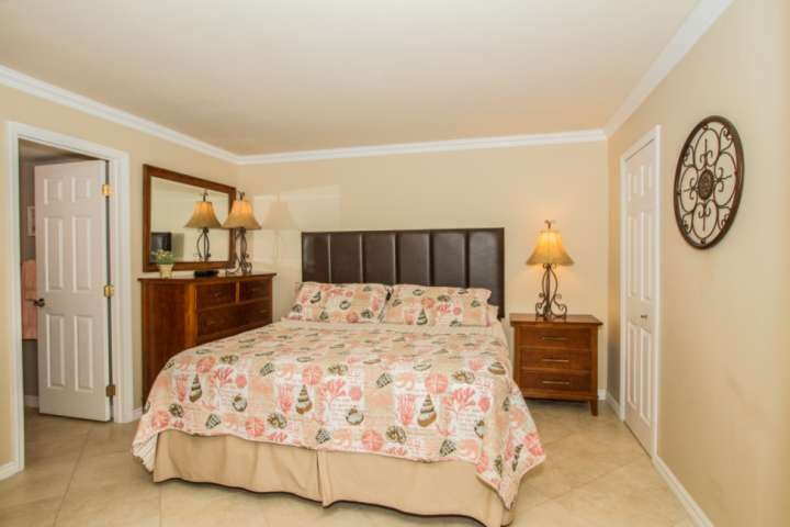 Comfortable King size bed with full dresser and walkin closet in spacious bedroom.