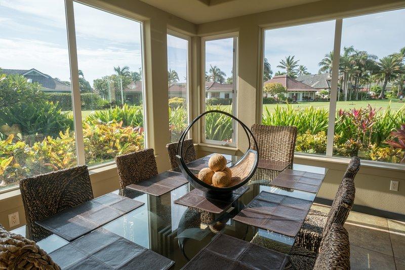 Salle à manger à côté de la cuisine avec baie vitrée donnant sur la ceinture de verdure.