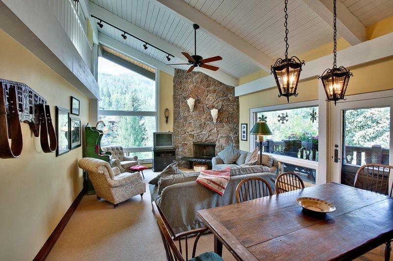 Dining area with seating for six and living room with gas fireplace.