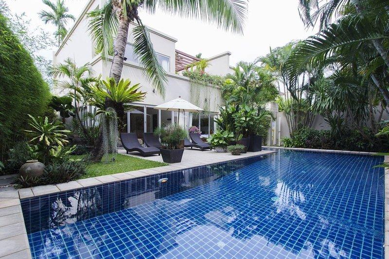 Hermoso jardín tropical con una gran piscina