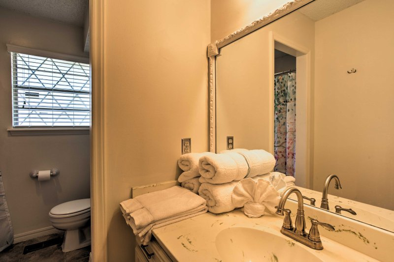 The main bathroom features a walk-in shower with textured glass doors.
