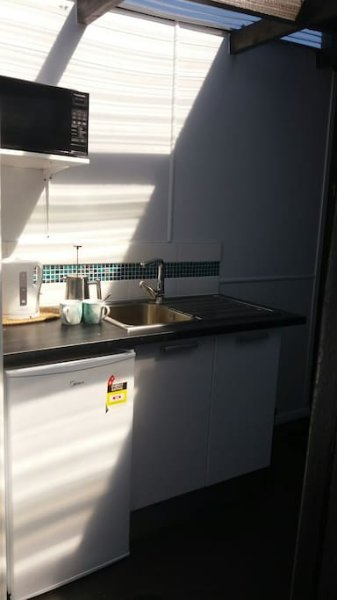 Kitchenette with hot/cold water, microwave, fridge and jug.