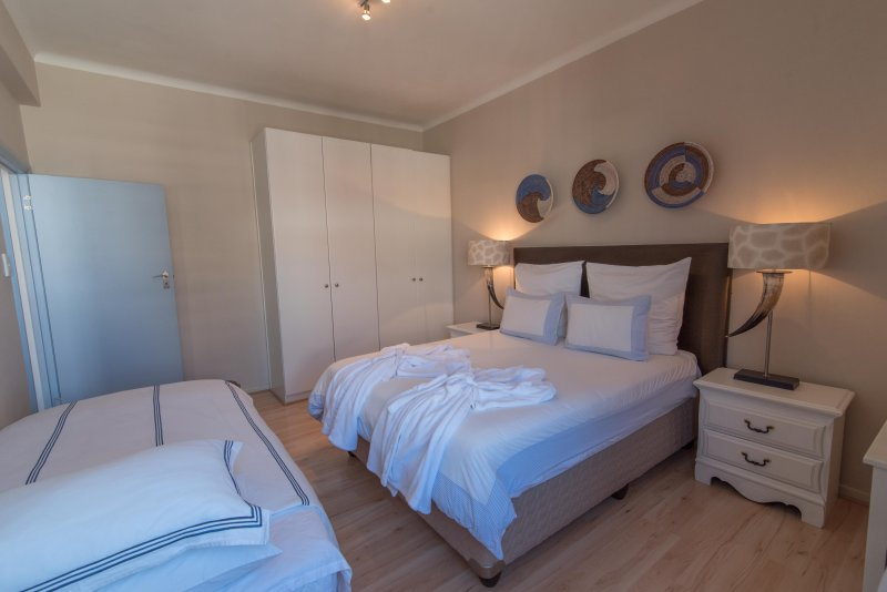 Beatiful luxurious bedroom with kingszie bed and a single bed. White linen and bath robes.