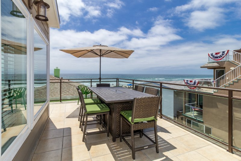 Expansive ocean views from upper deck, with large dining table and BBQ