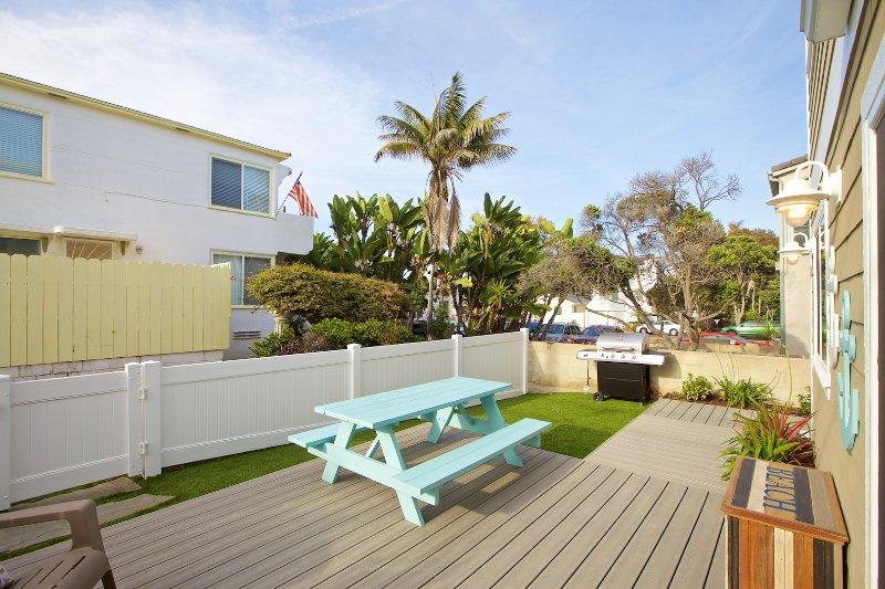 Grande pátio com churrasqueira e mesa, uma casa fora do oceano
