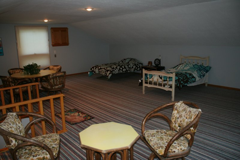 Loft with 2 twin beds, exterior fan to pull in cool lake air and game tables.